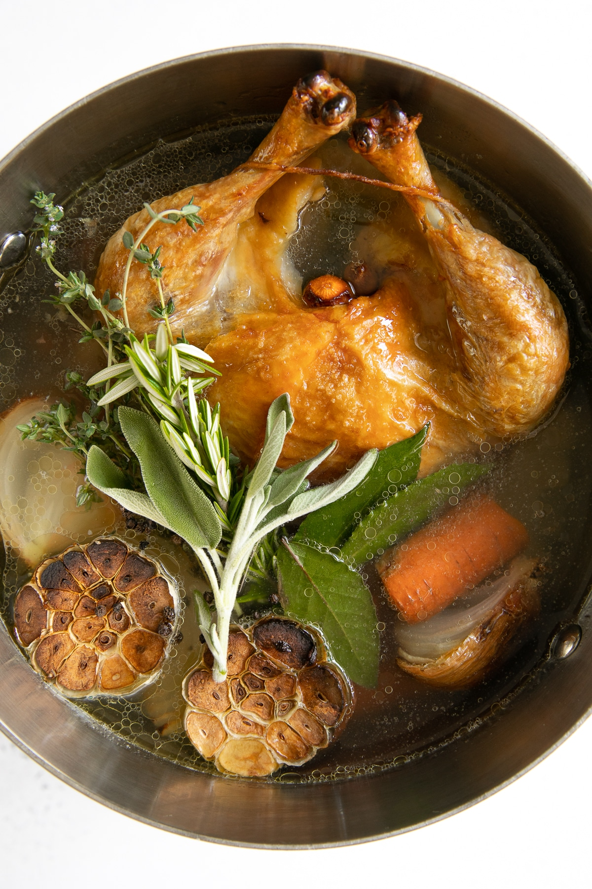 Large stock pot filled with one whole browned chicken, garlic, vegetables, and fresh herbs all covered in water.