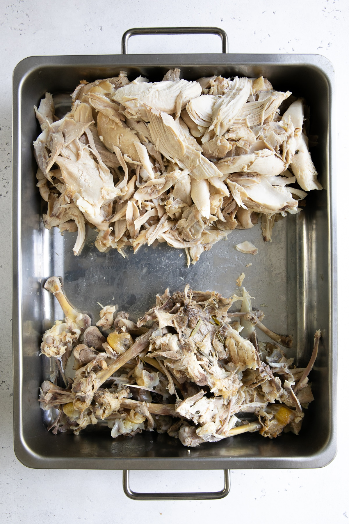 Large roasting pan with shredded chicken on one side and the chicken bones on the other.