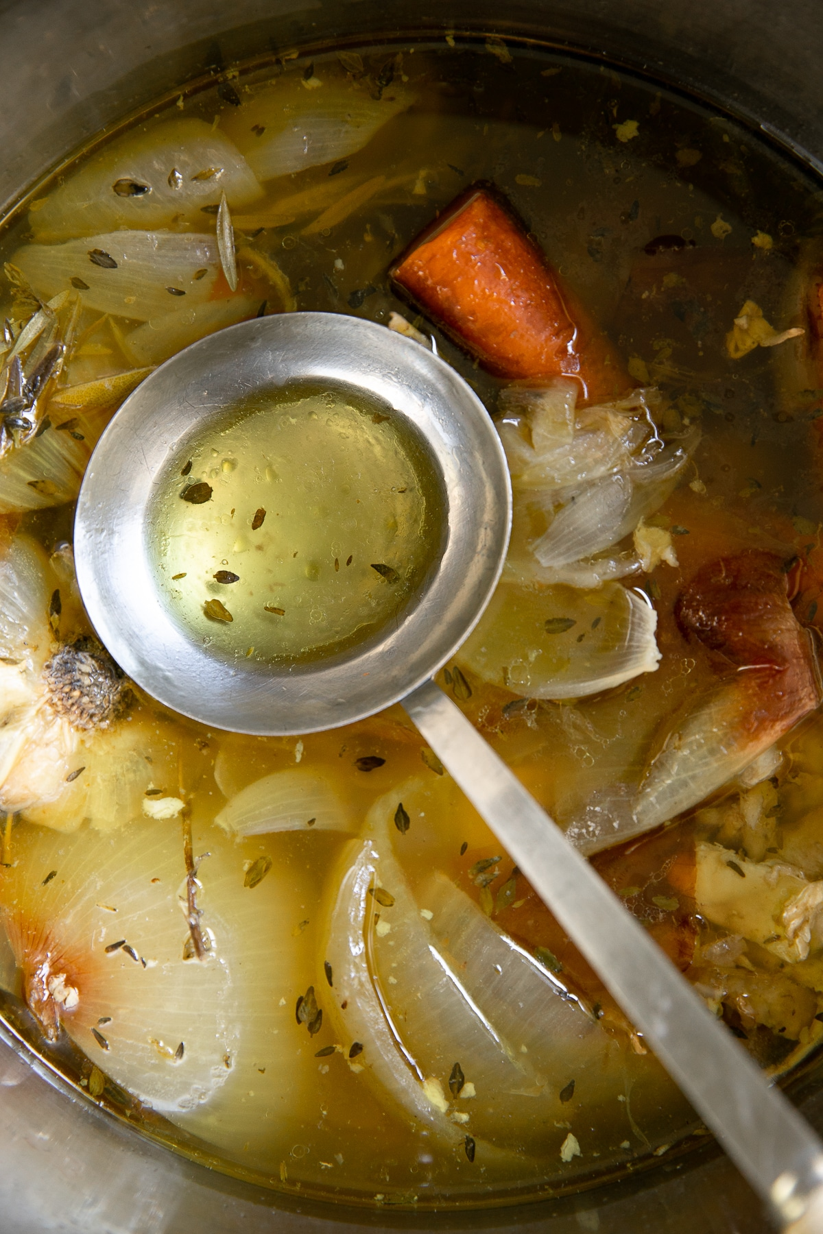 Ladle in a large pot filled with boiled chicken stock and roasting vegetables.