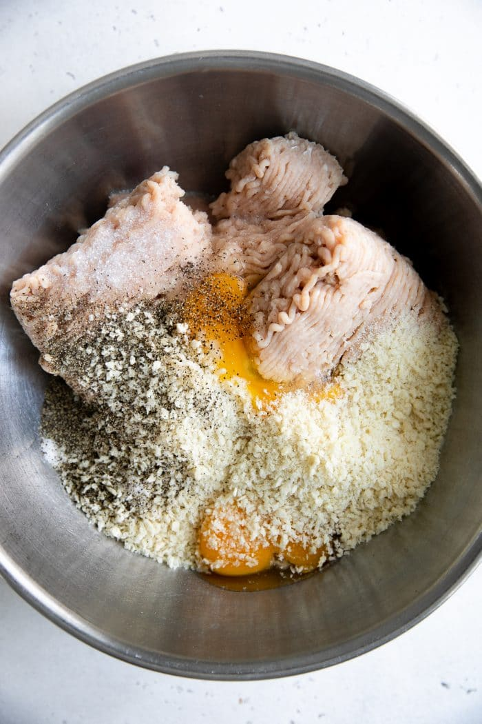 Ground turkey, breadcrumbs, eggs, and herbs in a large mixing bowl.
