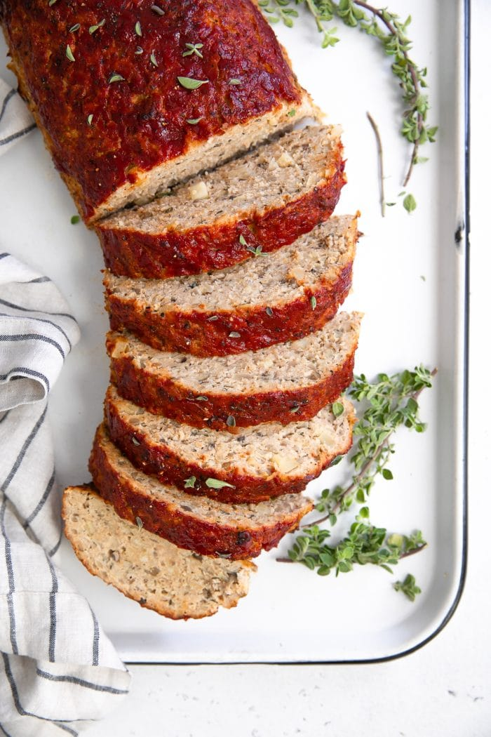 Overhead image of sliced meatloaf on a large white baking sheet.