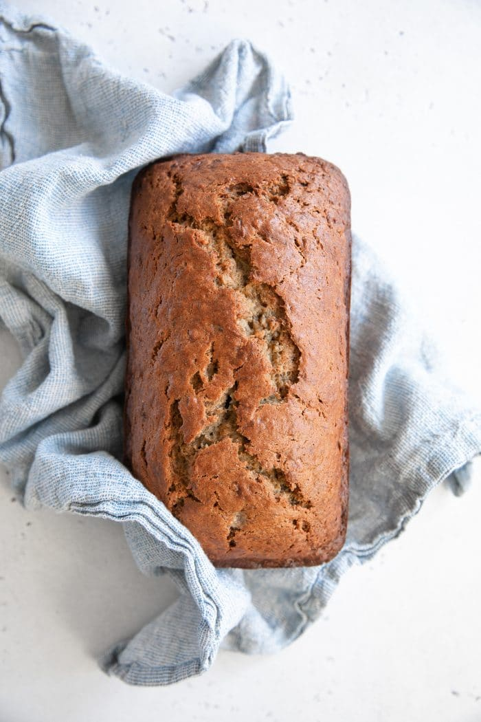 Fresh baked banana bread loaf wrapped in a light blue kitchen towel.