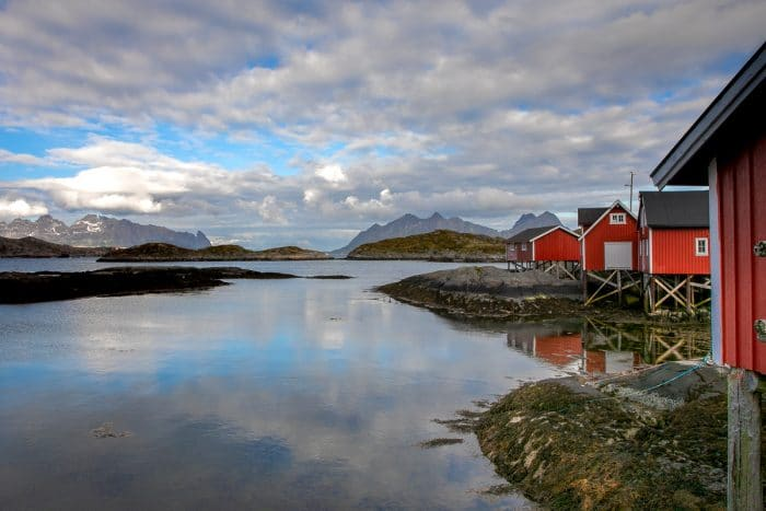 Red Norwegian huts on stilts near a body of water