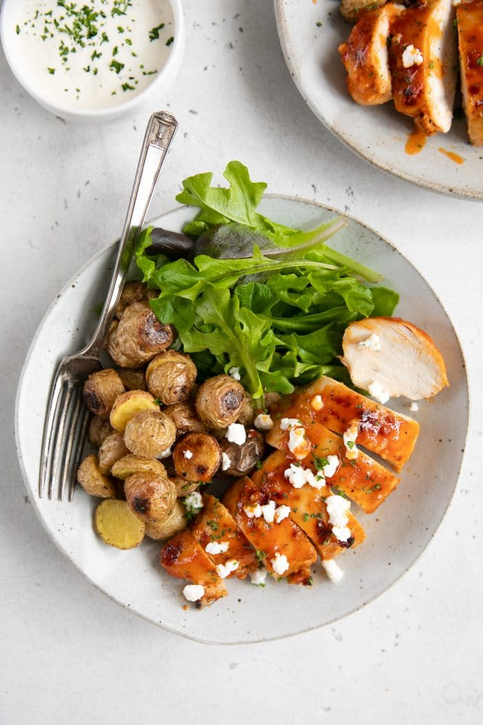 Overhead image of baked buffalo chicken breast sliced and plated on a white serving plate and served with mini roasted potatoes and fresh greens.