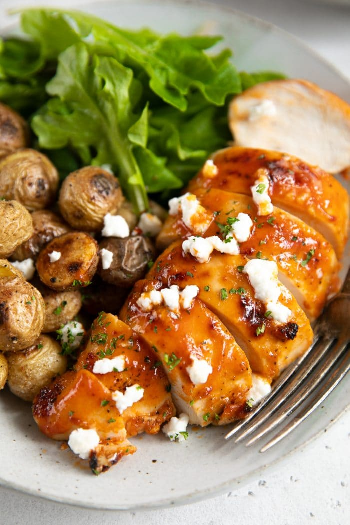 Baked buffalo chicken breast sliced and plated on a white serving plate and served with mini roasted potatoes and fresh greens.