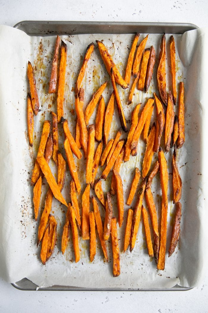 Crispy baked sweet potato fries on a large baking sheet.