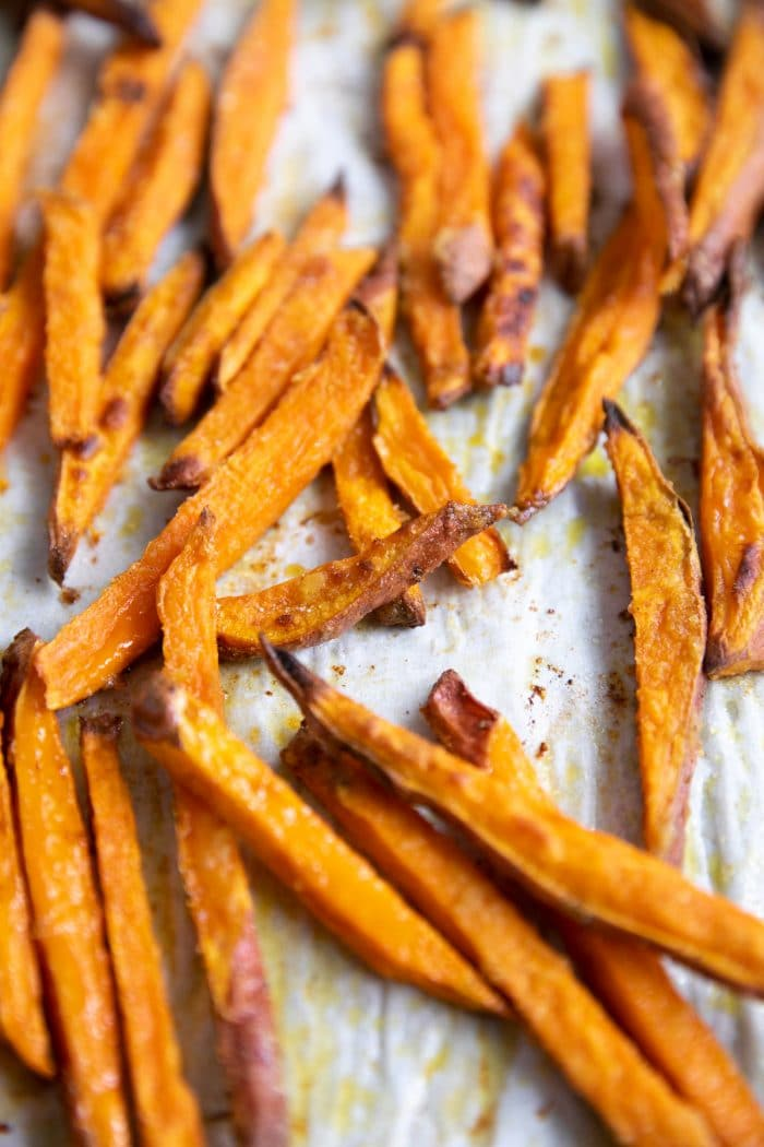 Close up image of oven baked sweet potato fries on a large baking sheet.