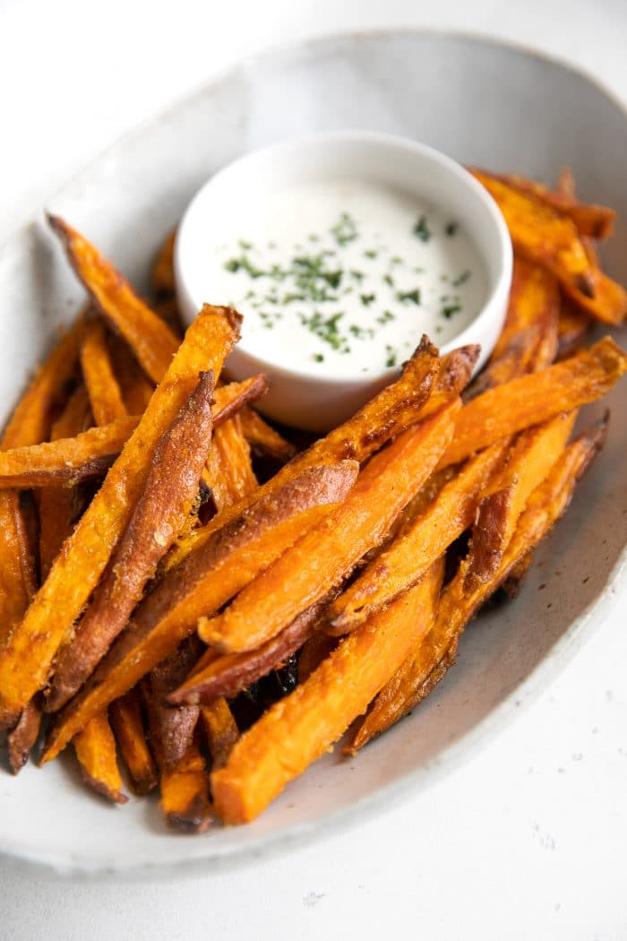 Oval serving dish filled with homemade baked sweet potato fries and served with ranch dressing.