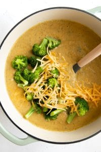 Large pot filled with cooked broccoli cheddar soup and topped with shredded cheddar cheese and blanched broccoli florets.
