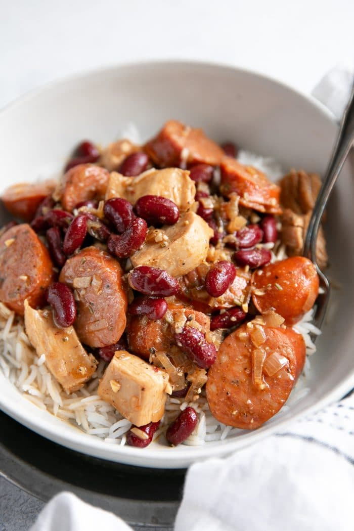 White bowl filled with spicy Cajun sausage, chicken, and red beans served over cooked white rice.