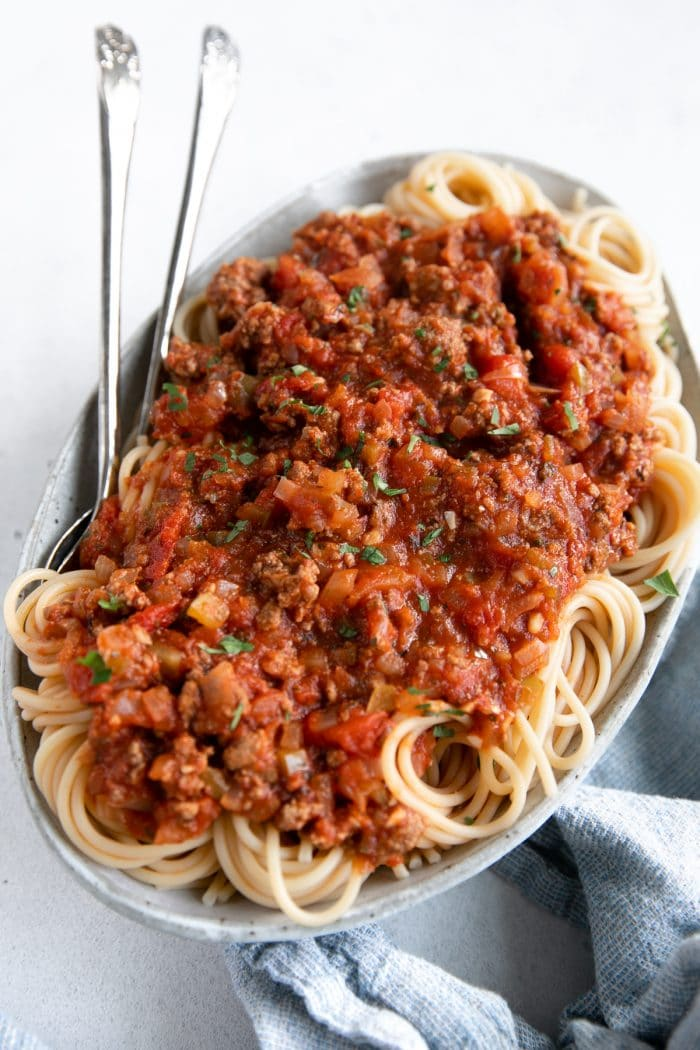 Large white serving plate filled with spaghetti noodles topped with homemade spaghetti sauce recipe.
