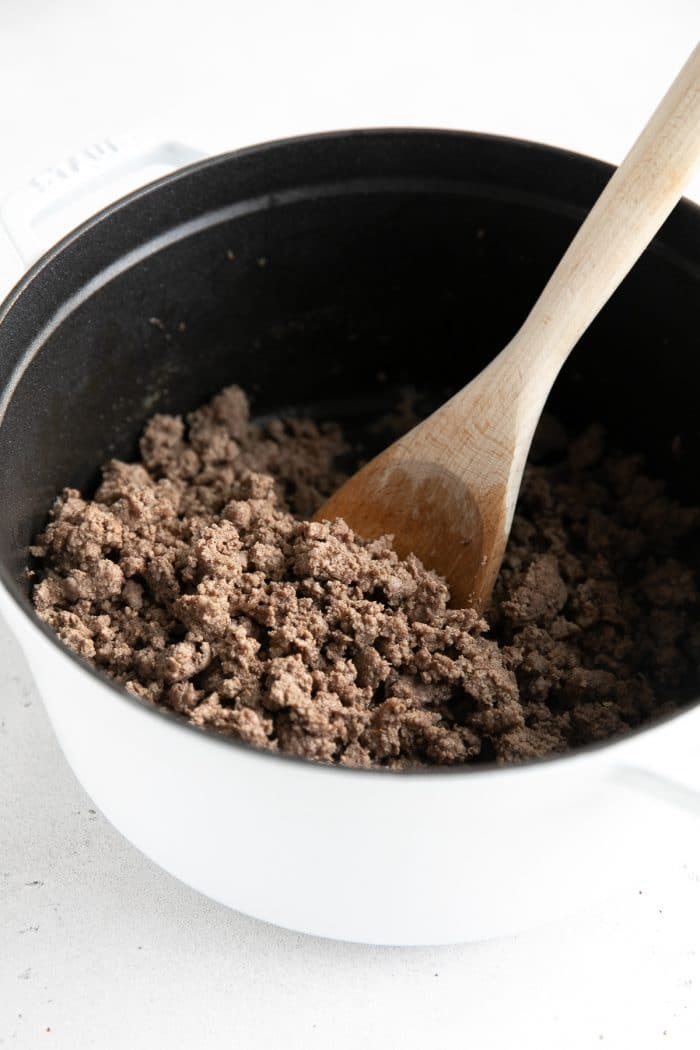 Ground beef cooking in a large white pot.