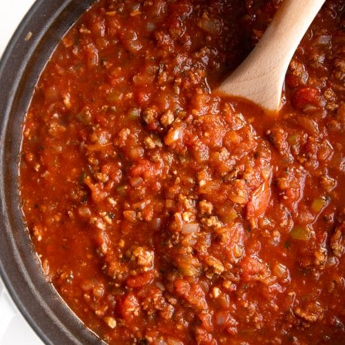 Overhead image of a large white pot filled with homemade spaghetti sauce made with onions, ground beef, garlic, and tomatoes.