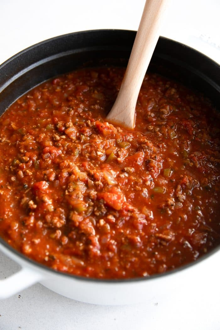 Large heavy-bottom pot filled with the best spaghetti sauce made with onion, garlic, tomato paste, tomatoes, and ground beef.