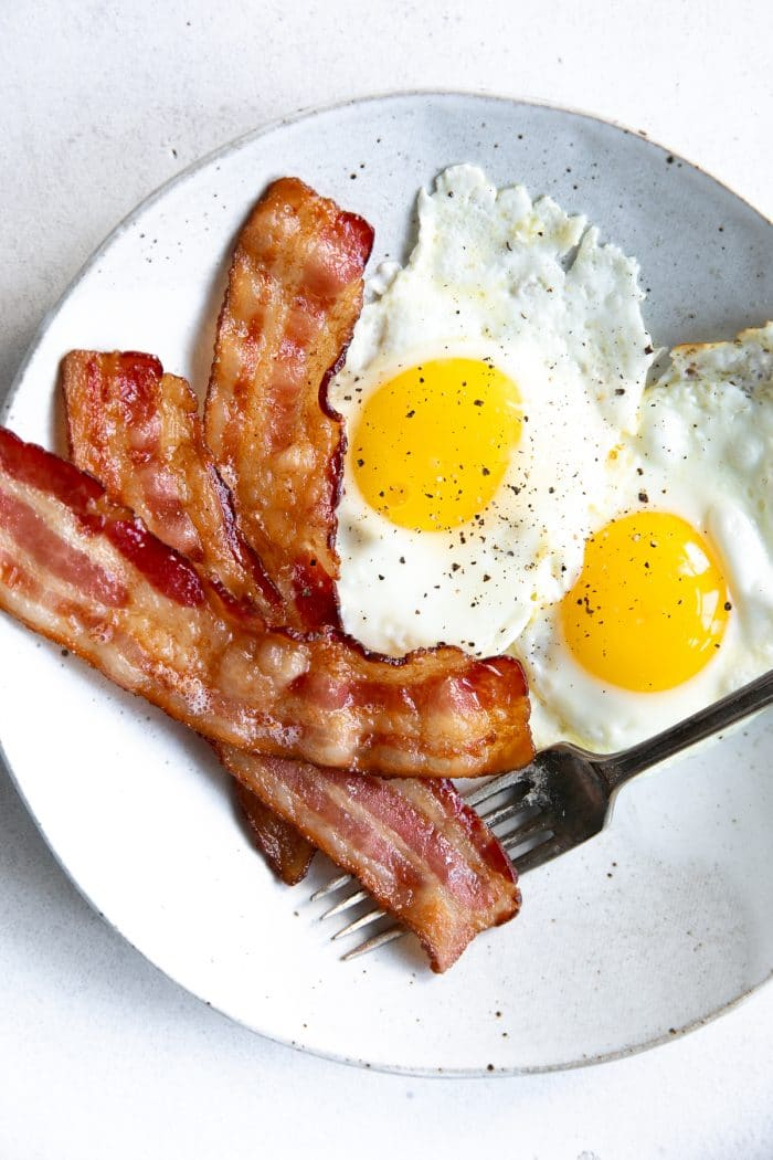 White plate with two sunny-side-up eggs and 3 pieces of bacon.