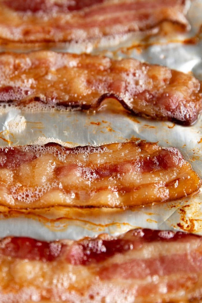 Fully cooked bacon on a baking sheet.