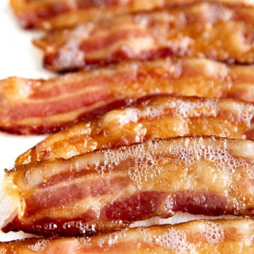 Fully cooked oven cooked bacon on a baking sheet lined with paper towels.