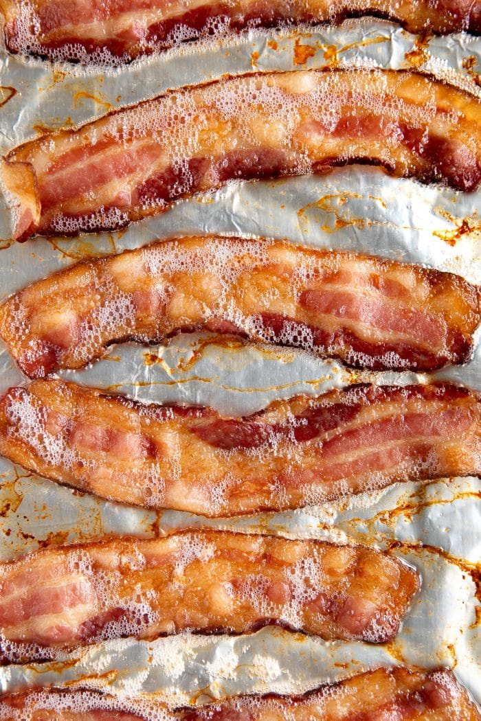 Overhead image of a baking sheet with fully-cooked bacon cooked in the oven.