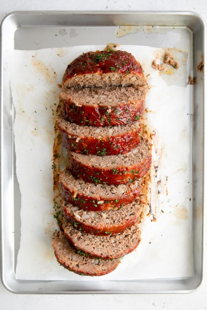 Large cooked meatloaf sliced into large thick slices.