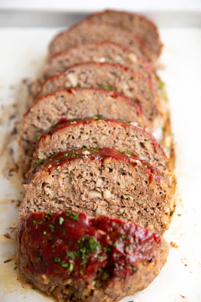 Sliced meatloaf topped with ketchup sauce and minced parsley.