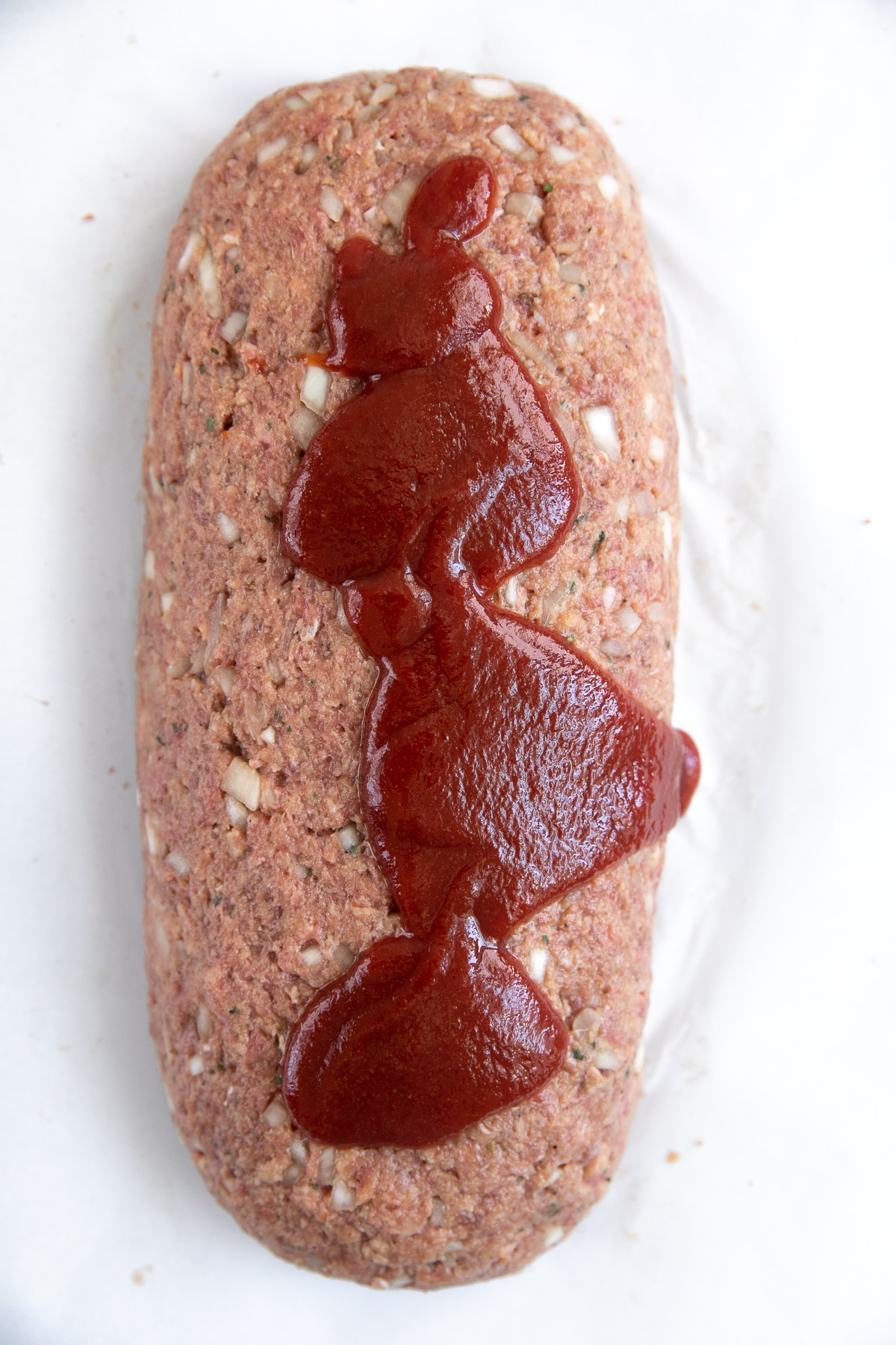 Unbaked beef meatloaf on a large parchment paper lined baking sheet topped with homemade ketchup sauce.