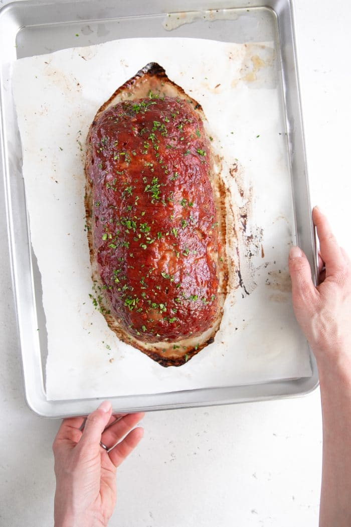 Hands holding a baking sheet with the best meatloaf. recipe.