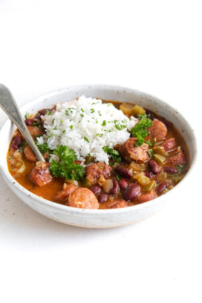 White shallow bowl filled with cooked red beans, andouille sausage, and topped with white rice.
