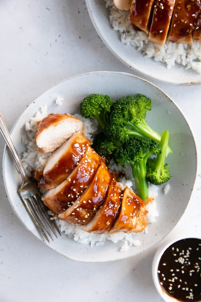 Overhead image of a white plate with cooked basmati rice, baked teriyaki chicken breast, and steamed broccoli.