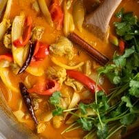Chicken curry recipe in a large heavy-bottomed pan with aromatics, cilantro, and bell pepper.