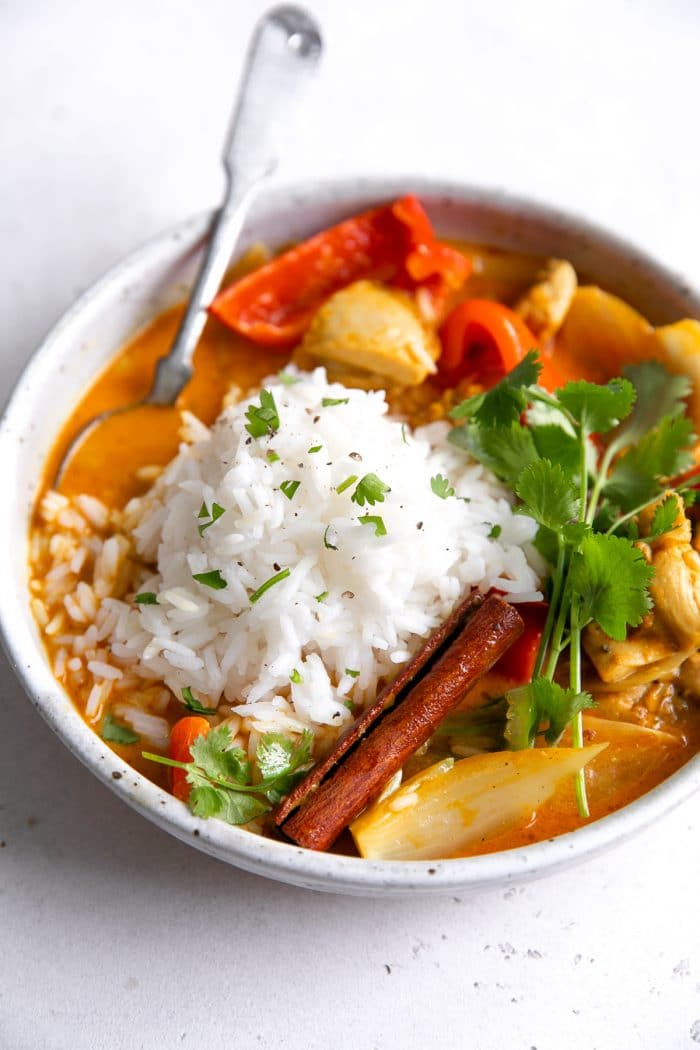 Colorful chicken curry in a large bowl and topped with white rice and fresh cilantro.
