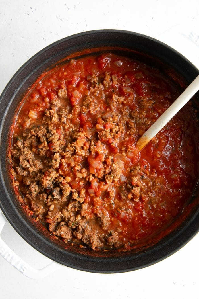 Overhead image of a pot filled with plant based ground meat mixed with homemade tomato sauce.