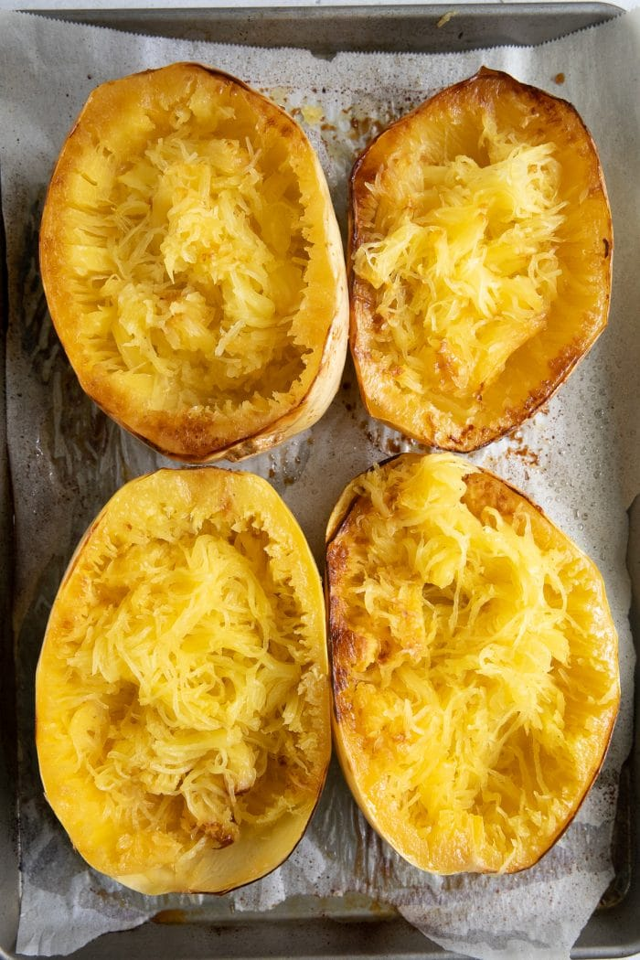 Overhead image of four baked spaghetti squash halves with squash noodles.