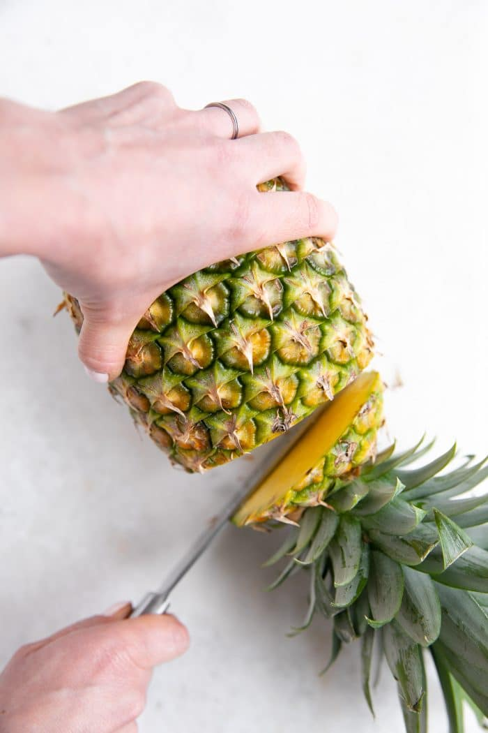 Cutting the top off of a pineapple.