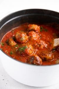 White stock pot filled with meatballs simmering in a homemade tomato sauce.