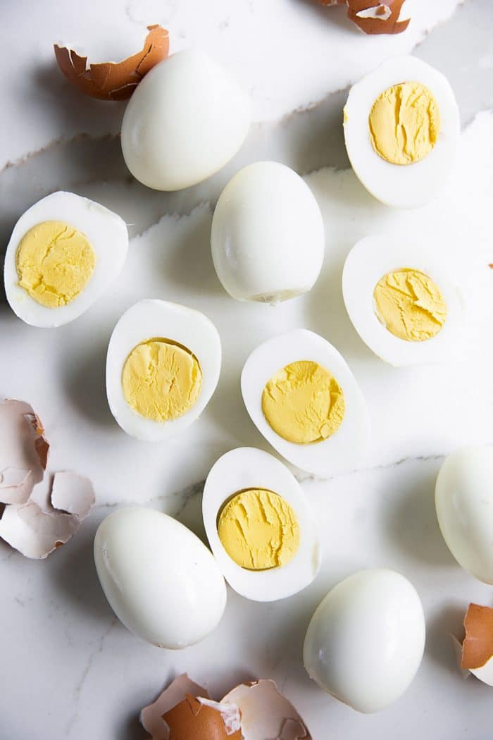 Perfect peeled hard boiled eggs, half have beef sliced in half lengthwise with a creamy yellow yolk.