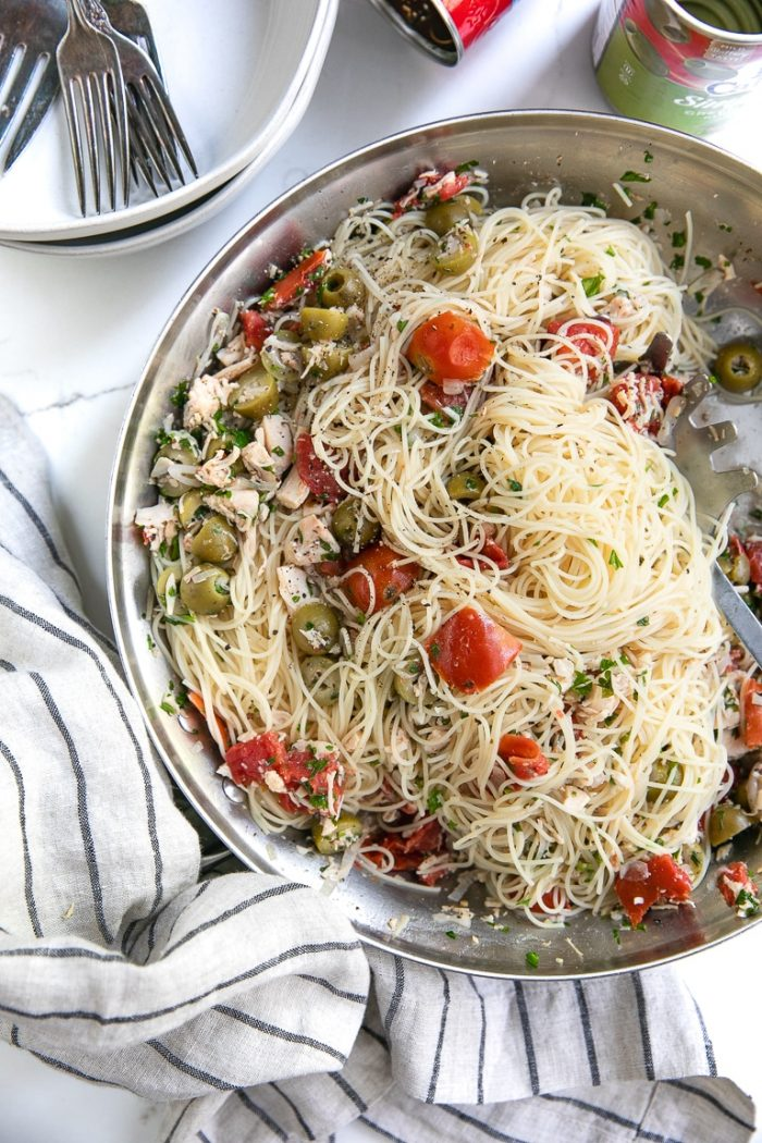 Skillet filled with canned tomatoes, olives, chicken and cooked angel hair pasta.