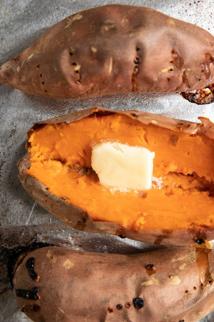 Baked sweet potatoes on a baking sheet one is sliced open and garnished with butter.