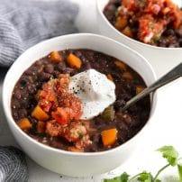 Two white bowls filled with black bean soup and garnished with fresh salsa and sour cream.