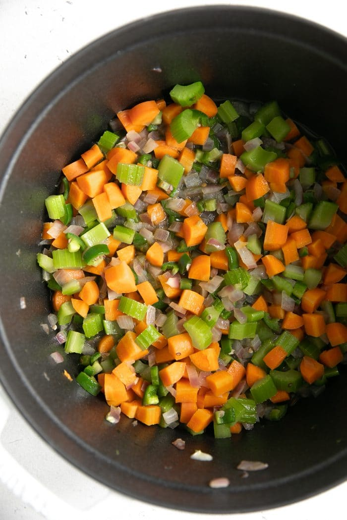 Large pot filled with cooking onions, celery, and carrots.