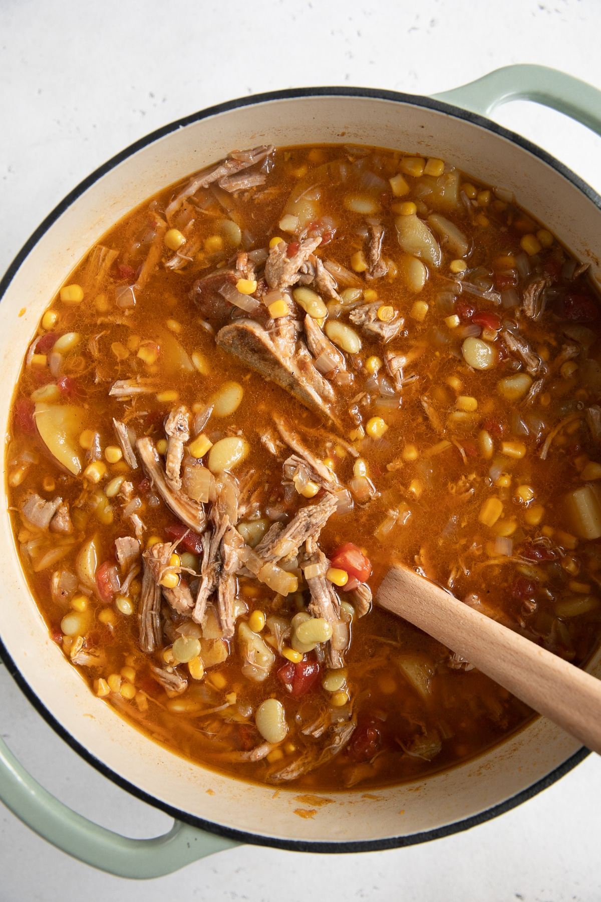 Large Dutch oven filled with a stew made with shredded pork, frozen lima beans, corn, tomatoes, potatoes, onions, and bbq sauce.
