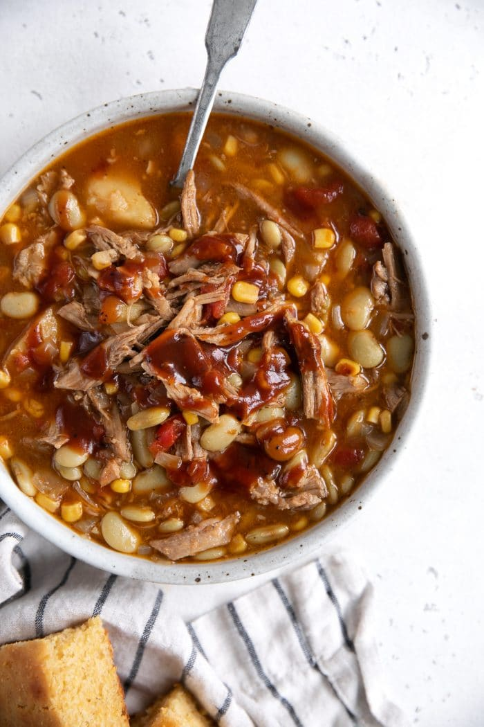 Over head image of a bowl filled with Brunswick stew and served with a side of freshly baked cornbread.