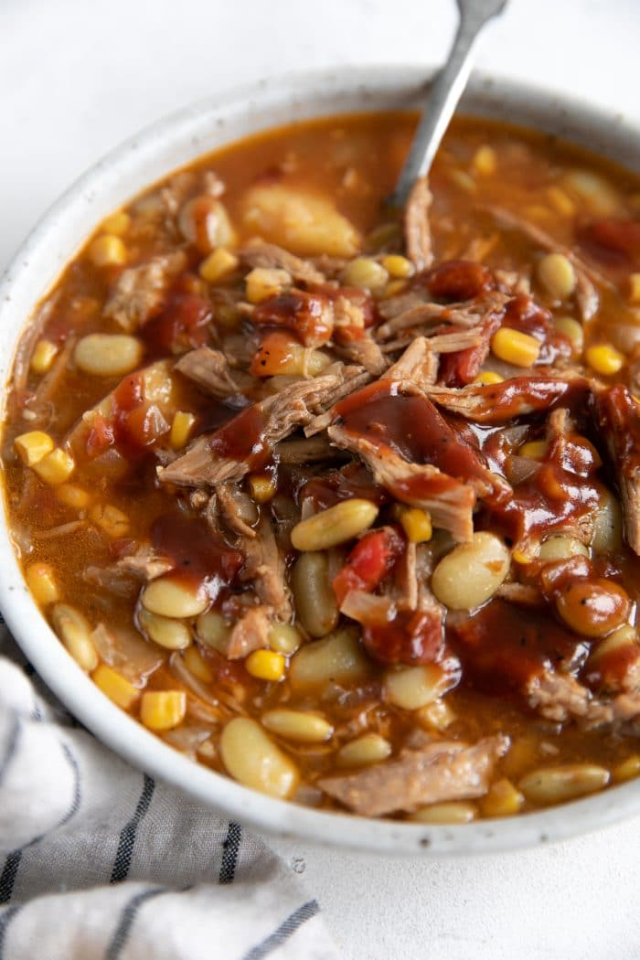 Large shallow bowl filled with Brunswick stew made with shredded pork and frozen lima beans.
