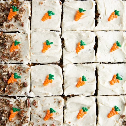 Carrot sheet cake sliced into 24 pieces and topped with individual handmade chocolate carrots and crushed pecans.