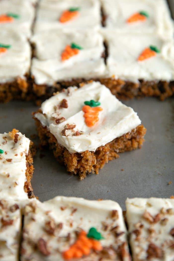 Slice of carrot cake sheet cake with cream cheese frosting topped with chopped pecans and chocolate carrot topper.