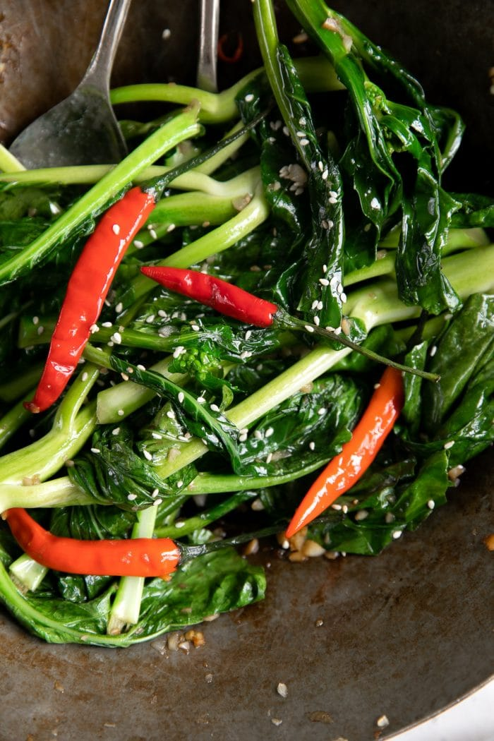 Large wok filled with stir fried Chinese broccoli in garlic and soy sauce with dried Thai chilis.