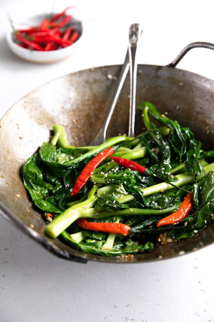 Large wok filled with Chinese broccoli, garlic, and Thai chilis.