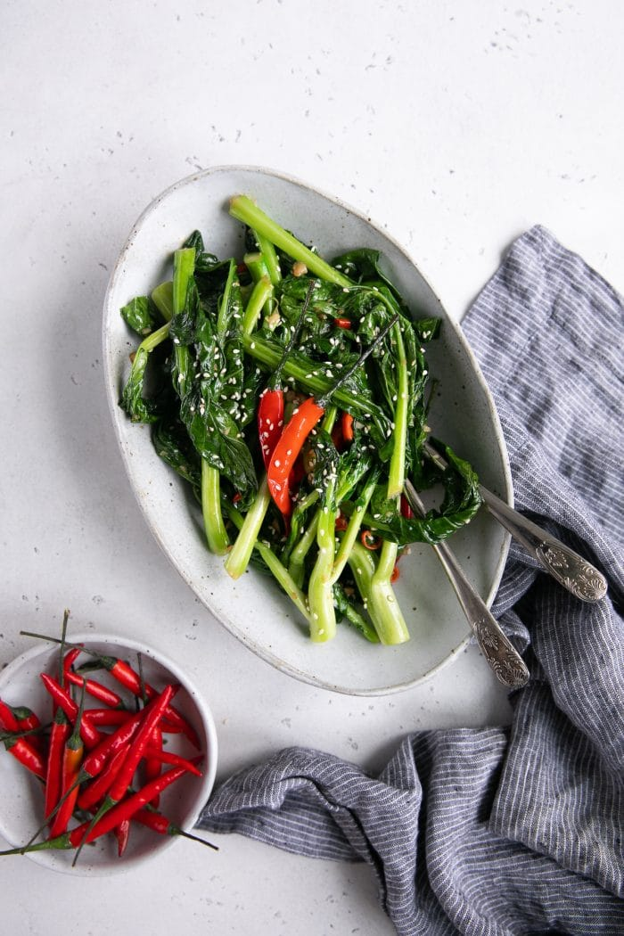 White serving plate filled with sauteed Chinese broccoli in soy sauce and garlic.