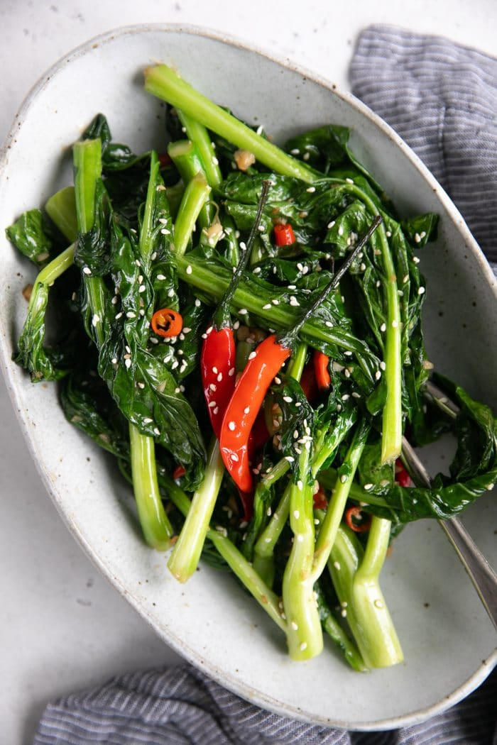 Oval serving plate filled with stir fried Chinese broccoli garnished with sesame seeds.