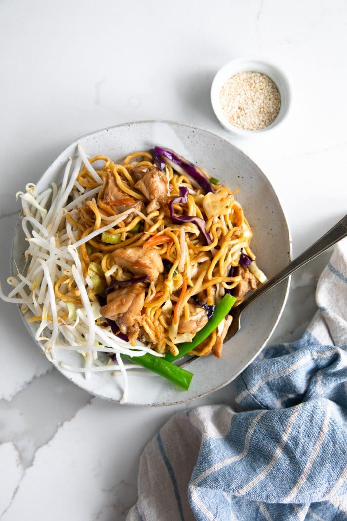 White plate filled with golden chow mein noodles with chicken and vegetables.