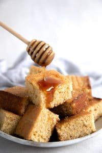 Honey being drizzled over freshly baked cornbread.